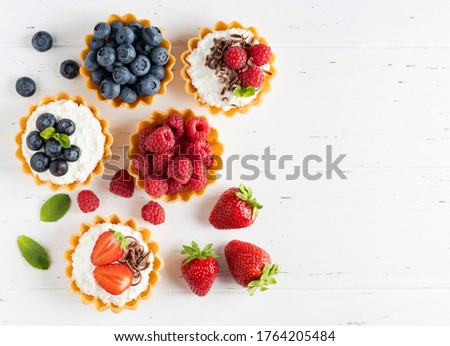 Fresh berries and ricotta cheese in tartletes. Summer dessert, healthy morning breakfast or snack, open sandwiches with strawberry, raspberry and blueberry. White wooden background. Top view.