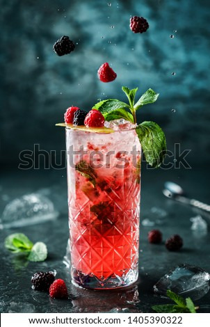Fresh berries cocktail with raspberry, blackberry, mint and ice in jar glass on dark blue background. Studio shot of drink in freeze motion, flying drops and berries. Summer cold drink and cocktail