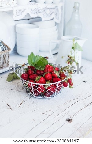 Fresh berries for metal basket over on rustic white kitchen shelves. - stock photo