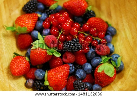 fresh berries fruit in wooden bowl includes strawberry, raspberry,blue berry,black berry etc. #1481132036