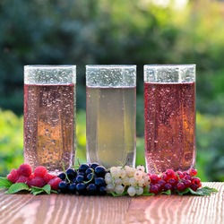 Fresh berries of black, red, white currants and red raspberries on the background of three transparent glasses filled with berry juice. Close-up. Side view. Shallow depth of field.