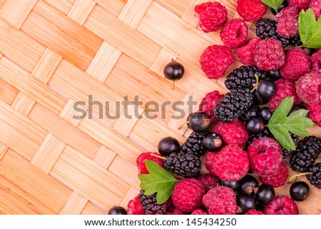 Fresh berries: raspberries, blackcurrants, mulberries on wicker background - stock photo