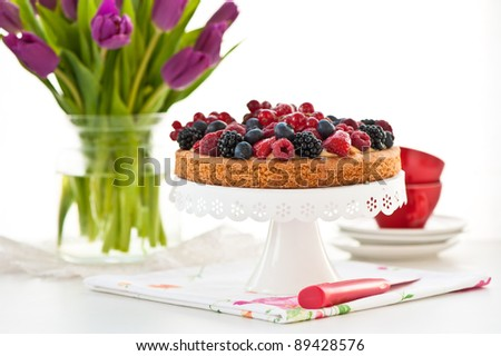 fresh berries tart on a cake-stand and purple tulips