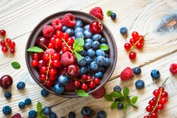 Fresh berries. Various  summer berries in a bowl on rustic wooden table.