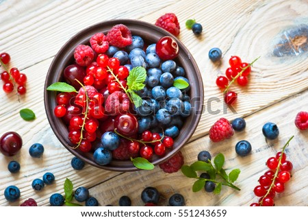 Fresh berries. Various  summer berries in a bowl on rustic wooden table. #551243659