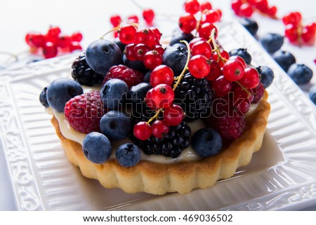 Fresh berry tartlet or cake filled with custard, raspberry, blueberry redcurrant and blackberry  delicious dessert for the whole family and easy diet. Close up