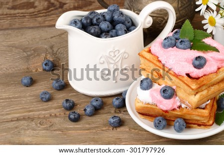 Fresh biscuits with bilberry mousse and blueberry and milk in a transparent jug on a wooden background.