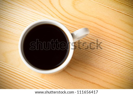 Fresh Black Coffee in a White Ceramic Cup on a Wooden Table - stock photo