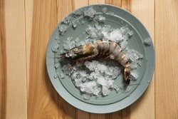 Fresh black tiger shrimp with ice on wooden table, top view