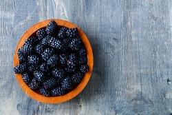 Fresh blackberries in wooden bowl. Top view.