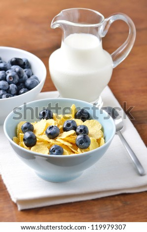 Fresh blueberries and milk in a bowl of cornflakes