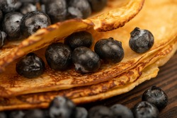Fresh blueberries and traditional Russian pancakes. Shrovetide week of the end of winter. Close-up selective focus.