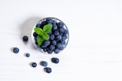 fresh blueberries in glass bowl on white wooden background, top view