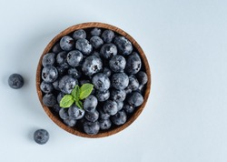 Fresh blueberries in wooden bowl with mint leaf on blue background. Raw berries with the drops of water. Top view. Cop space.