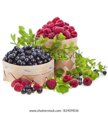 fresh blueberries , raspberries in the basket on white