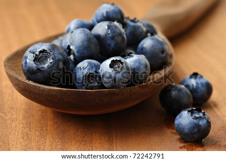 Fresh blueberries spilling from vintage wooden spoon onto wood table.  Macro with extremely shallow dof.