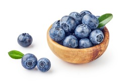 Fresh blueberries with blueberry leaves in wooden bowl isolated on white background.