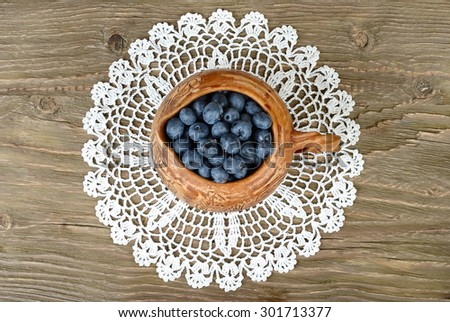 Fresh blueberry in a clay small jug on a lacy napkin on a wooden background. Top view.