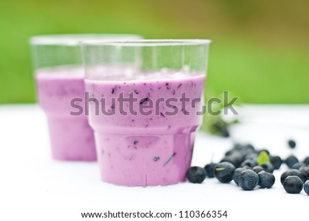 fresh blueberry in container and glass on wooden table