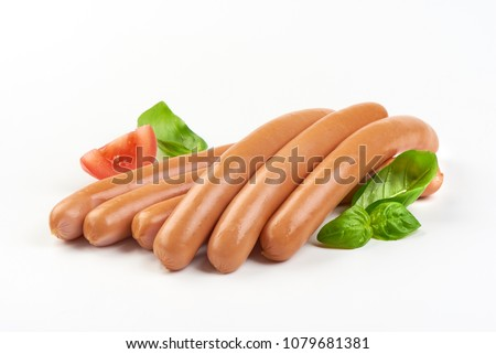 Fresh boiled Wiener sausages with green herbs and vegetables isolated on the white background.