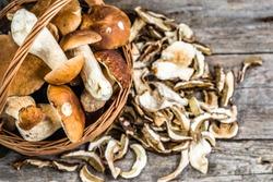 Fresh boletus mushrooms in a basket and dry mushroom on wooden table, overhead