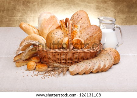Fresh bread and pastry with milk on jug
