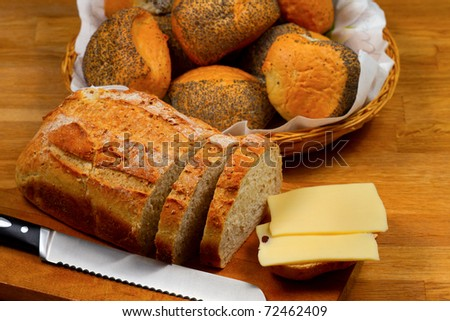Fresh bread cheese and knife on wooden cutting board with basket with bread rolls in the background