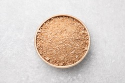 Fresh bread crumbs in bowl on grey table, top view