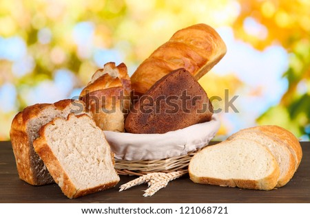 Fresh bread in basket on wooden table on natural background
