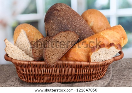 Fresh bread in basket on wooden table on window background