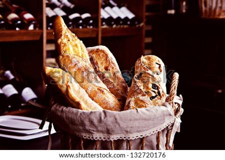 Fresh bread in basket witn bottles of wine on background