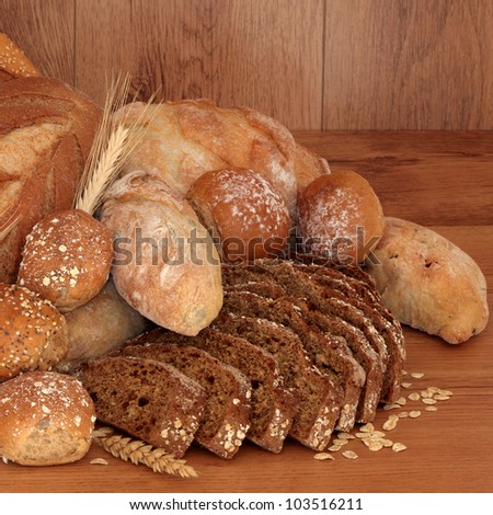 Fresh bread loaf and roll collection over oak background.