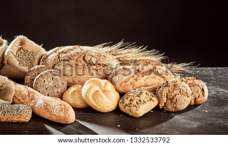 Fresh bread loaves assortment piled on dark table surface with grains of rye and wheat, against black background #1332533792