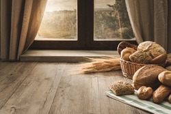 Fresh bread on the kitchen table in front of a window with a countryside panorama, healthy eating and traditional bakery concept