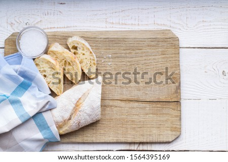 Fresh bread slice and cutting knife on cutting board on the white background. Flat lay. Top view. Stock photo ©