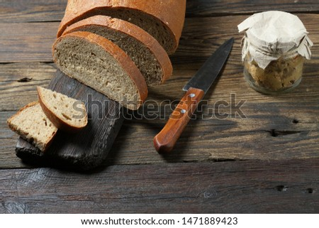 Fresh bread slice and cutting knife on rustic table #1471889423