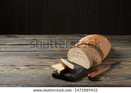 Fresh bread slice and cutting knife on rustic table #1471889432