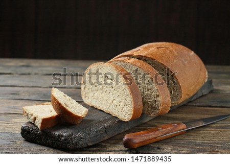 Fresh bread slice and cutting knife on rustic table #1471889435