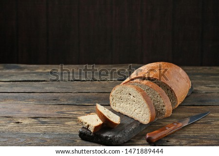 Fresh bread slice and cutting knife on rustic table #1471889444