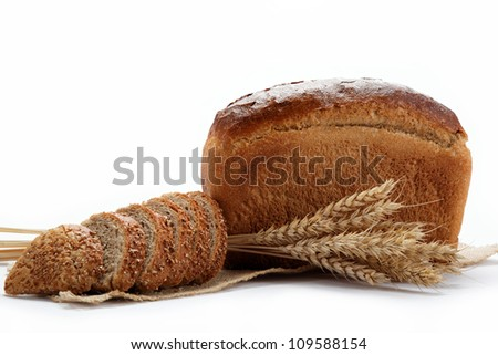 Fresh bread with ears of wheat on the canvas.