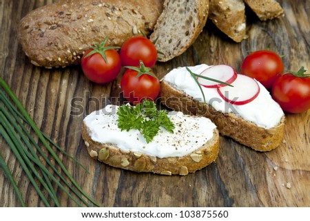 fresh bread with herb curd dinner on wooden background