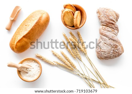 fresh bread with wheat flour in bakery shop on white desk background top view