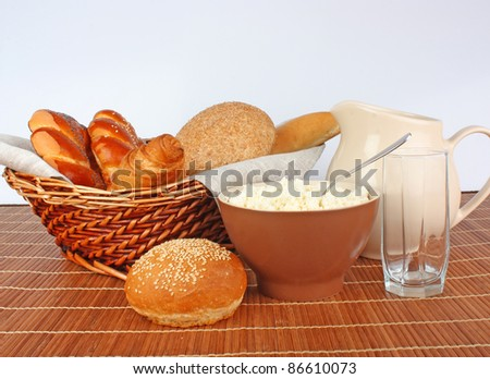 Fresh breads and milk in jug and glass, cottage cheese in bowl, food photo
