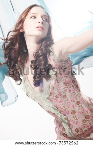 Fresh breeze is waving a piece of silk fabric behind a beautiful young girl