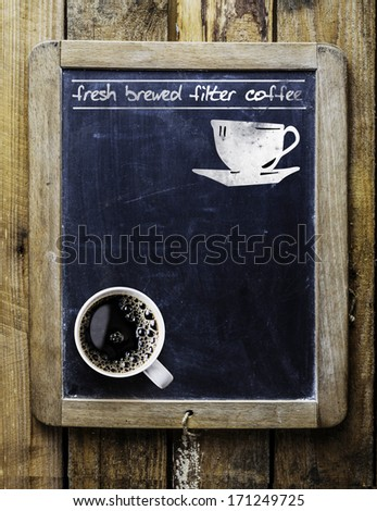Fresh brewed filter coffee - handwritten on an old vintage school slate used as an advertising sign in a rustic coffee shop with a fresh cup of aromatic coffee in the bottom corner