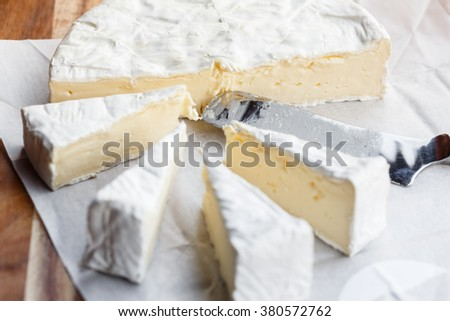 Fresh Brie cheese and slices on wooden table with knife
