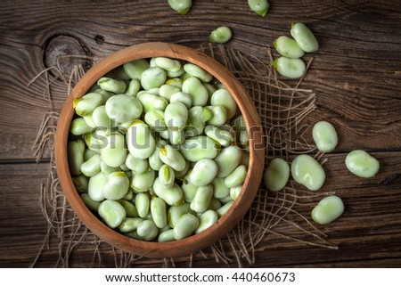 Fresh broad beans in a container on a wooden table. Selective focus. Top view.
