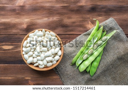 Fresh broad green beans pod (pea) on wooden table. Top view.