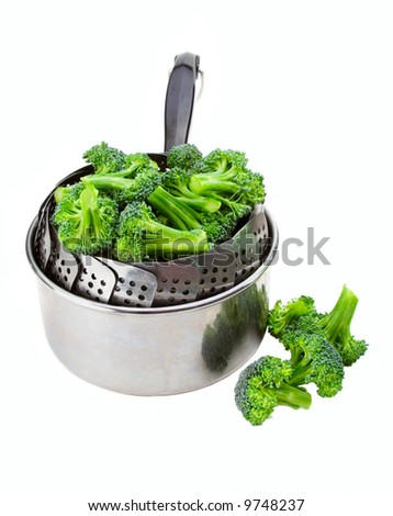 Fresh broccoli loaded into a steamer and saucepan, ready for steaming. - stock photo
