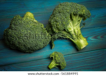 Fresh broccoli on a blue wooden table #561884995